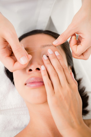 eyebrow: Close up view of hands threading beautiful womans eyebrow Stock Photo
