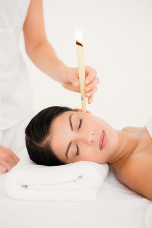 ear: Close up of a beautiful woman receiving ear candle treatment at spa center Stock Photo