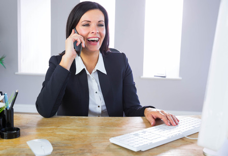 middleaged: Businesswoman working at her desk in her office