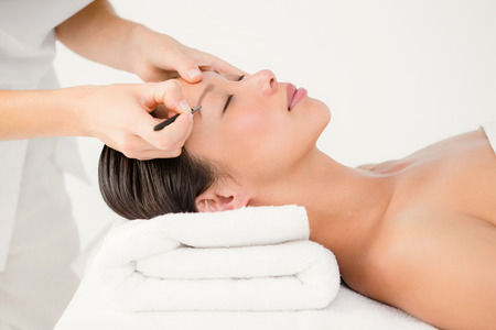 Woman using tweezers on patient eyebrow at the health spa