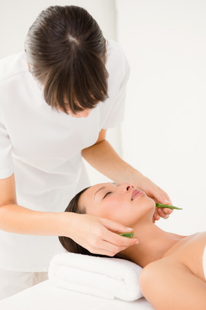 Attractive young woman receiving aloe vera massage at spa center Imagens