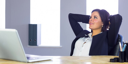 office desk: Businesswoman relaxing at her desk in her office