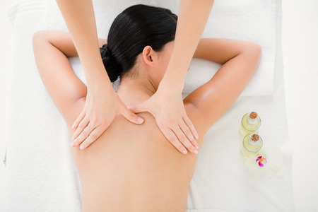 massage: Upward view of woman receiving back massage at spa center Stock Photo