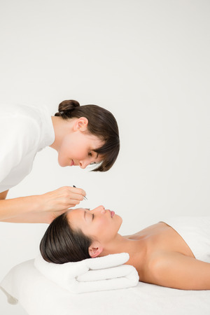 tweezers: Woman using tweezers on patient eyebrow at the health spa