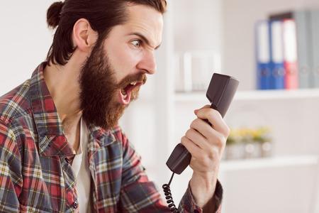 enojo: Hipster hombre de negocios enojado que hace una llamada en su oficina Foto de archivo