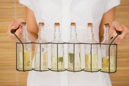 carying: Close up view of woman holding bottles of oil massage Stock Photo