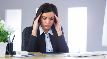 Stressed businesswoman working at her desk in her office