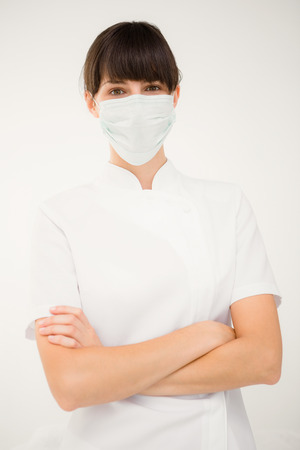 protective mask: Nurse wearing protective mask with arms crossed on white background
