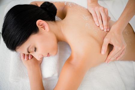 tratamientos corporales: Mujer que disfruta de un masaje exfoliante de sal en el centro de rehabilitación