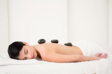 calor: Mujer bonita que disfruta de un masaje con piedras calientes en el spa de salud