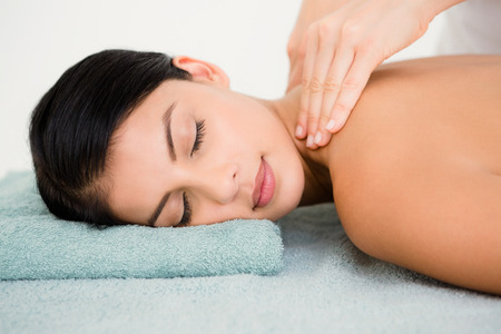 massage  table: Beautiful brunette on a massage table at spa center Stock Photo