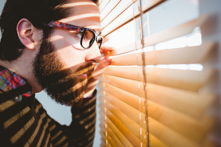 Hipster businessman peeking through blinds in his office Stock Photo
