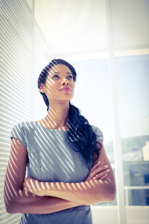 the thoughtful: Thoughtful businesswoman standing in the office looking away Stock Photo