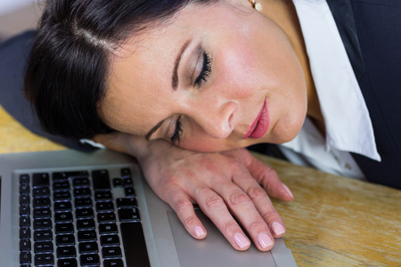 office desk: Businesswoman taking a nap on her desk in her office
