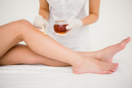 depilacion con cera: Mediados de sección de terapeuta mujer depilación piernas al centro de spa Foto de archivo