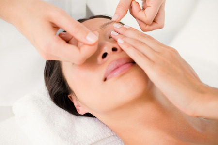 threading: Close up view of hands threading beautiful womans eyebrow Stock Photo