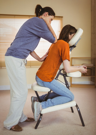 elbow chair: Young woman getting massage in chair in therapy room Stock Photo