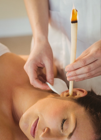 human ear: Young woman getting an ear candling treatment in therapy room Stock Photo