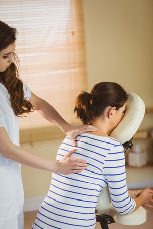 chair massage: Young woman getting massage in chair in therapy room Stock Photo