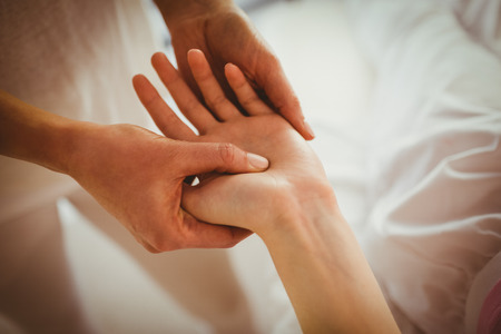 masajes relajacion: Mujer que consigue masaje joven de la mano en la sala de terapia Foto de archivo