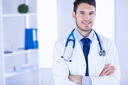 medical office: Portrait of smiling doctor looking at camera with arms crossed in medical office Stock Photo