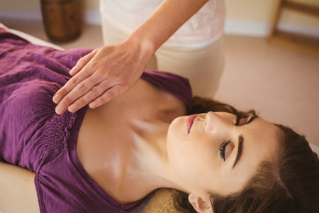 thirties: Young woman having a reiki treatment in therapy room