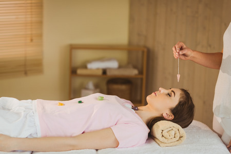 crystals: Young woman at crystal healing session in therapy room