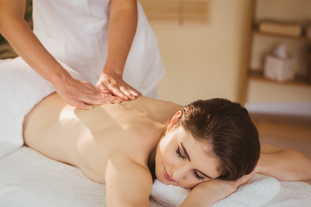 massage: Young woman getting back massage in therapy room Stock Photo
