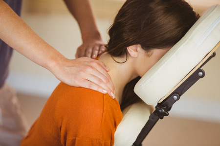 massage: Jeune femme se massage dans le fauteuil dans la salle de thérapie