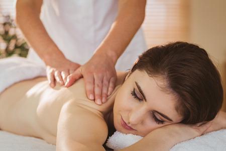 masajes relajacion: Joven mujer recibiendo masaje de espalda en sala de terapia Foto de archivo