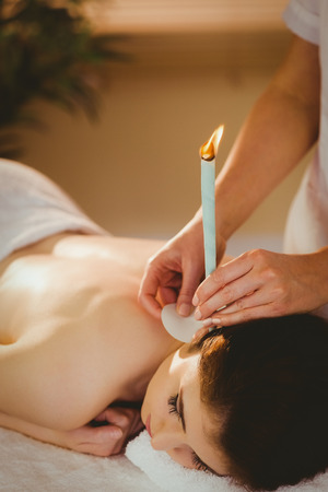therapy room: Young woman getting ear candling treatment in therapy room