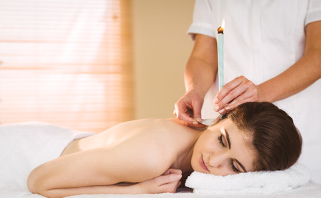ear: Young woman getting ear candling treatment in therapy room