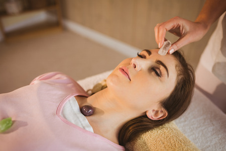 alternative healing: Young woman at crystal healing session in therapy room