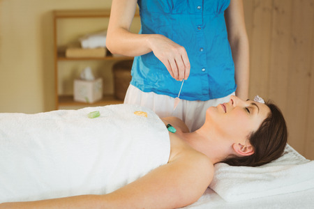 crystal healing: Young woman at crystal healing session in therapy room
