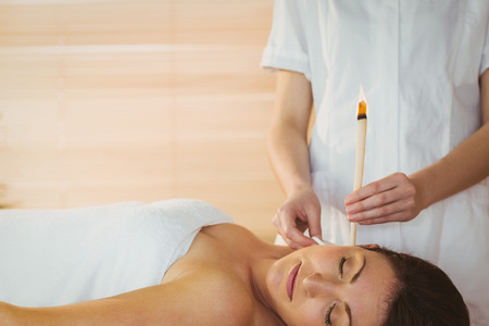 therapy room: Young woman getting an ear candling treatment in therapy room Stock Photo