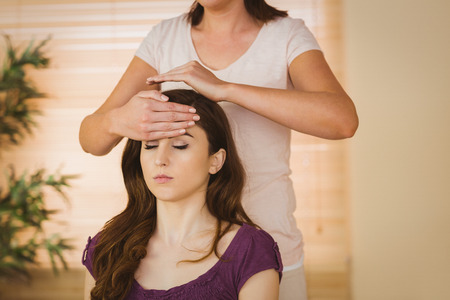 Young woman having a reiki treatment in therapy room