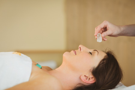 chakra healing: Young woman at crystal healing session in therapy room