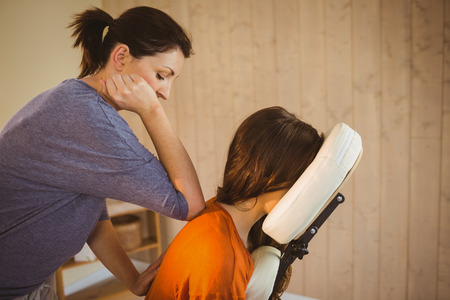 massage chair: Young woman getting massage in chair in therapy room Stock Photo