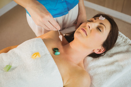crystal therapy: Young woman at crystal healing session in therapy room