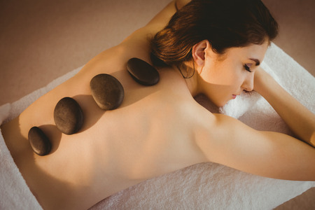 stone: Young woman getting a hot stone massage in therapy room