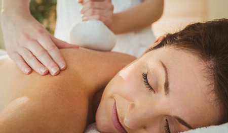 therapy room: Young woman getting herbal compress massage in therapy room