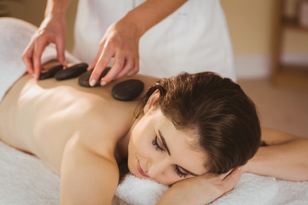 stone therapy: Young woman getting a hot stone massage in therapy room
