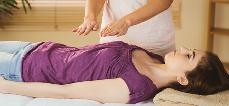 heal: Young woman having a reiki treatment in therapy room