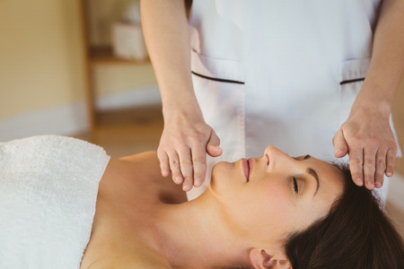 reiki: Young woman having a reiki treatment in therapy room