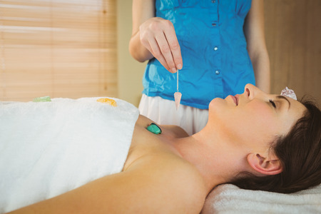 healing: Young woman at crystal healing session in therapy room