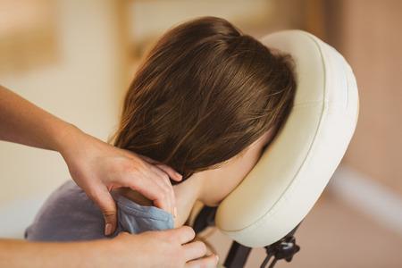 massaggio: Giovane donna che ottiene massaggio in sedia in camera di terapia