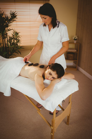 therapy room: Young woman getting a hot stone massage in therapy room