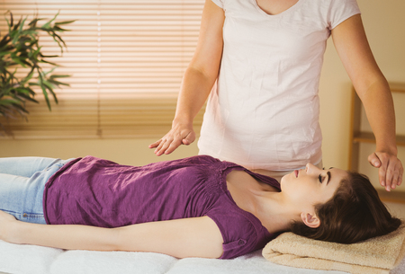 chakra: Young woman having a reiki treatment in therapy room