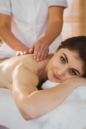 therapy room: Young woman getting shoulder massage in therapy room