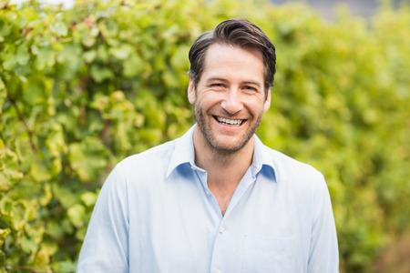 Jonge gelukkig man lacht naar de camera in de druif velden